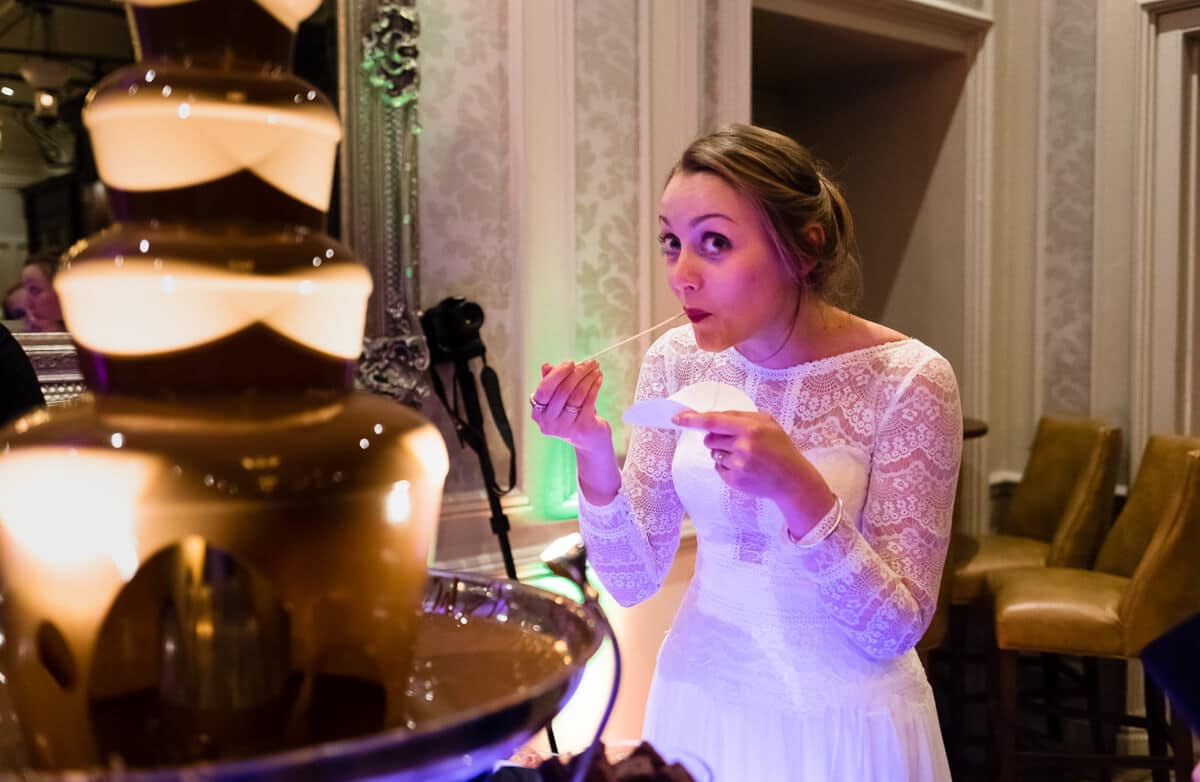 Bride with cheeky look eating chocolate