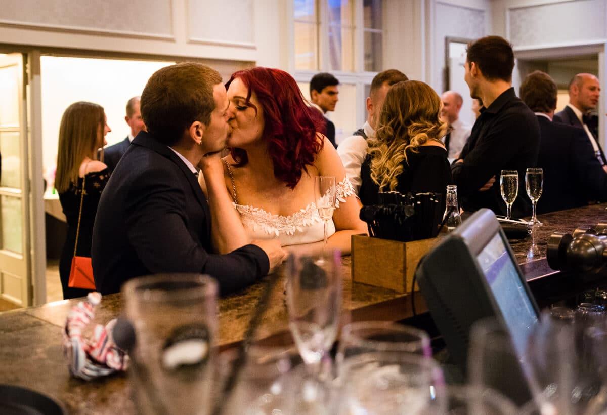Wedding guests kissing at bar