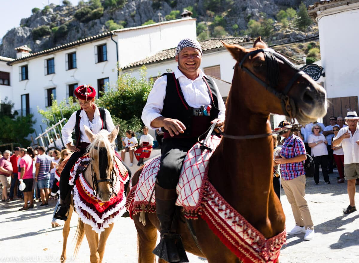 Man and woman riding horses wearing colourful costumes at Andalusian fiesta