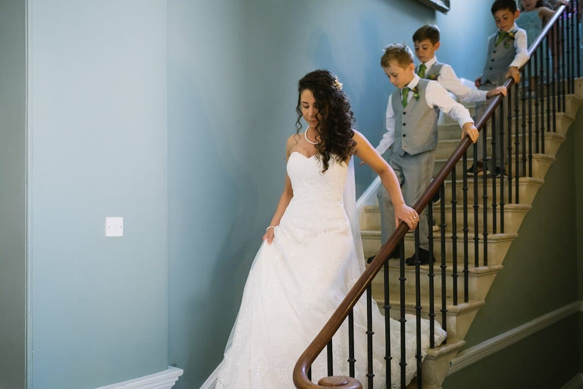 Bride and page boys descending stairs at Summer wedding