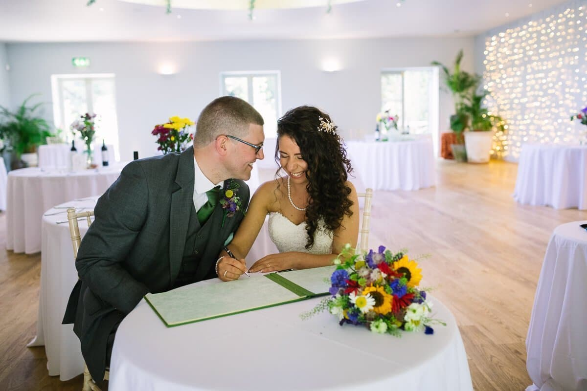 Bride and groom sign the registrar