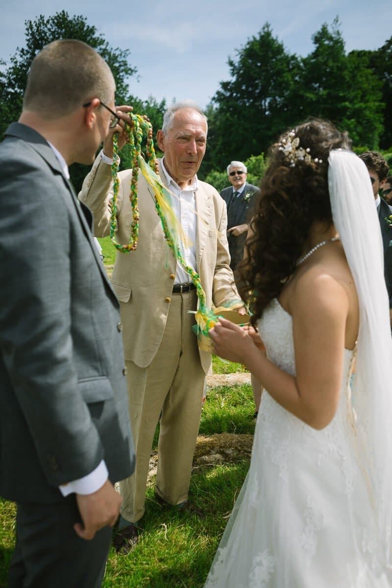 Bride and groom are presented with ribbons at rural wedding ceremony