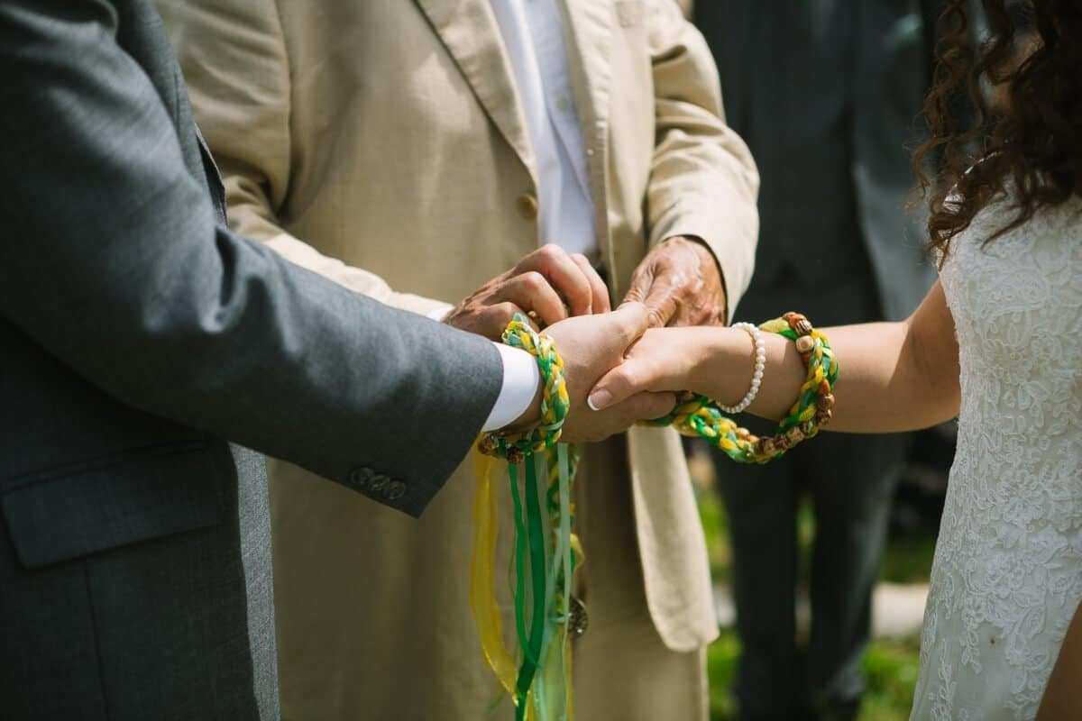 Wedding couples hands are tied with ribbon