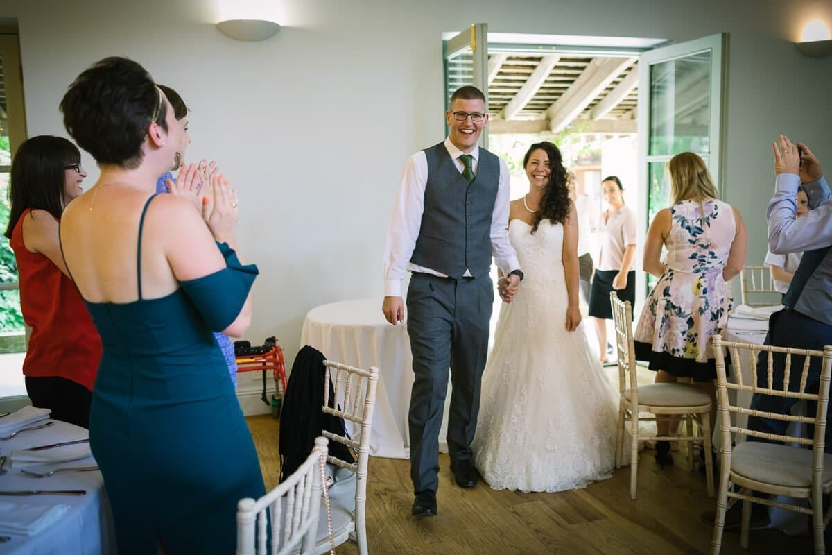 Bride and groom enter dining room with wedding guests cheering