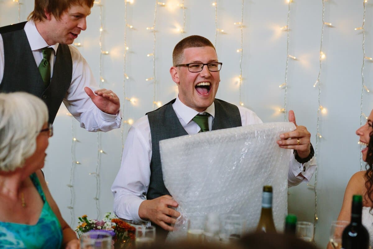 Groom laughing at wedding speeches