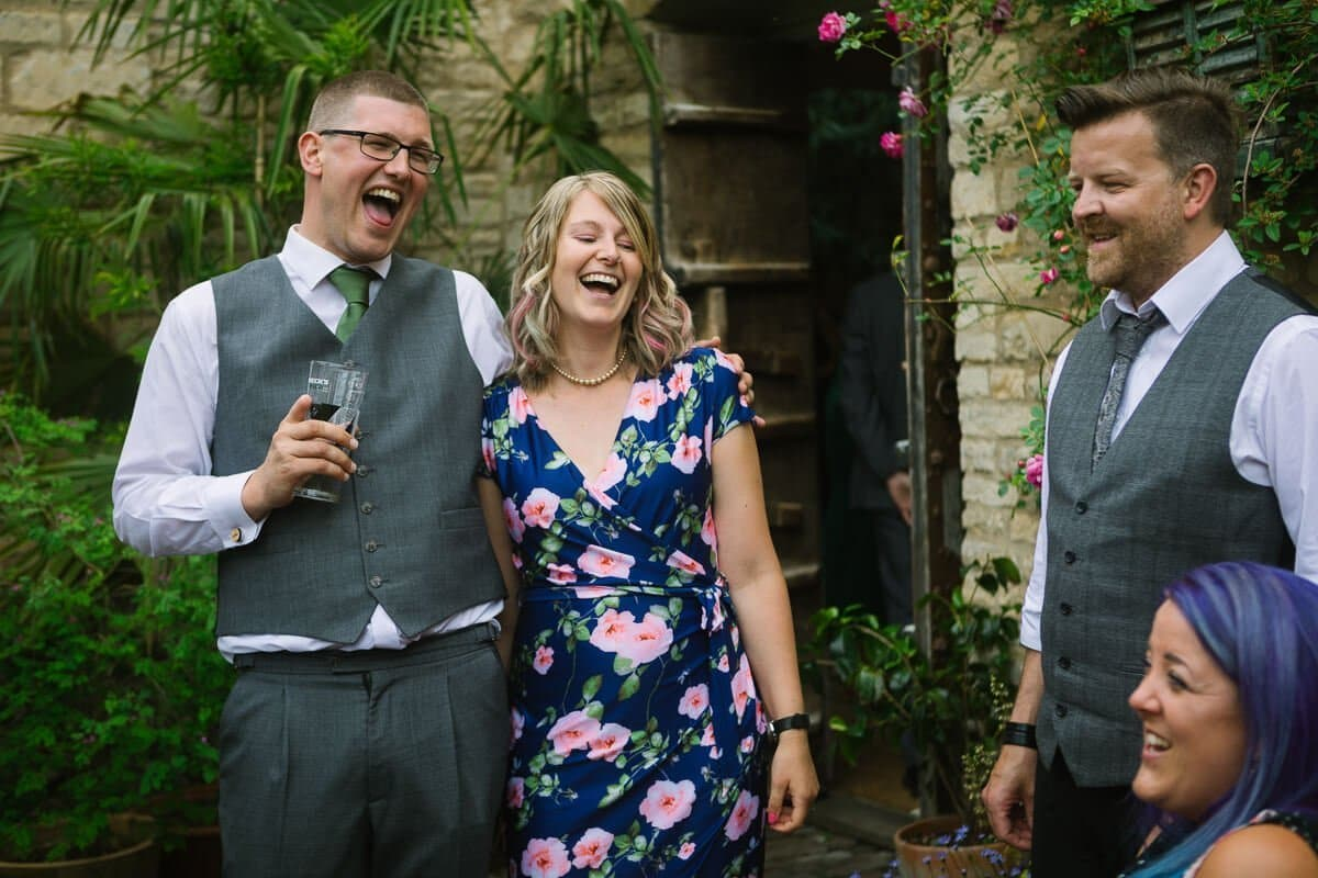 Groom laughing with wedding guest