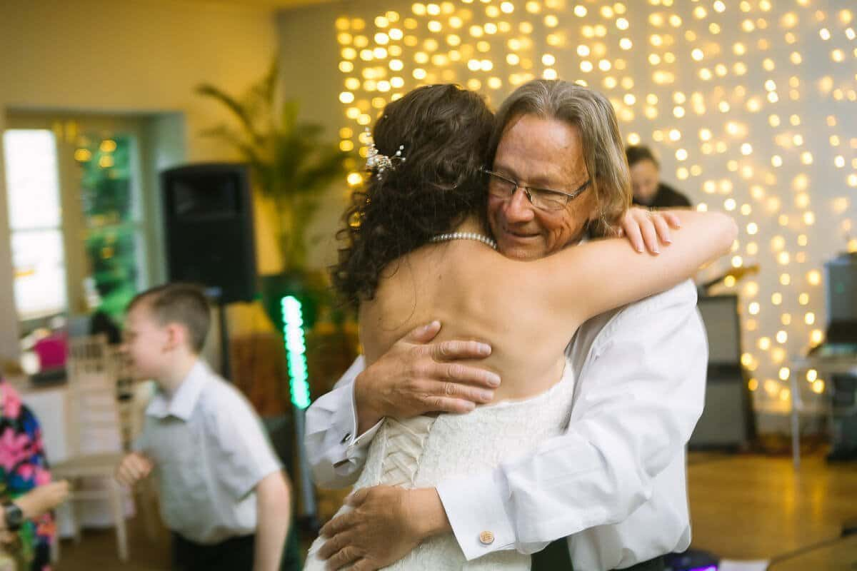 Father of bride hugging his daughter on the dance floor