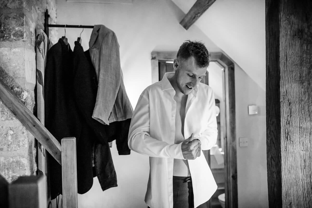 Groom putting on shirt at wedding preparations