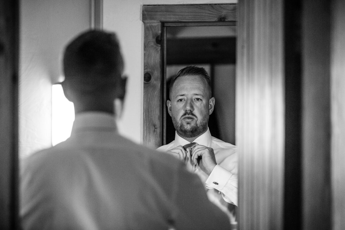 Groom looking in mirror and putting on tie at Cotswold Wedding at Cripps Barn