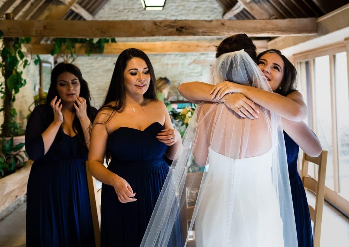 Bridesmaid hugging bride at Barn Wedding