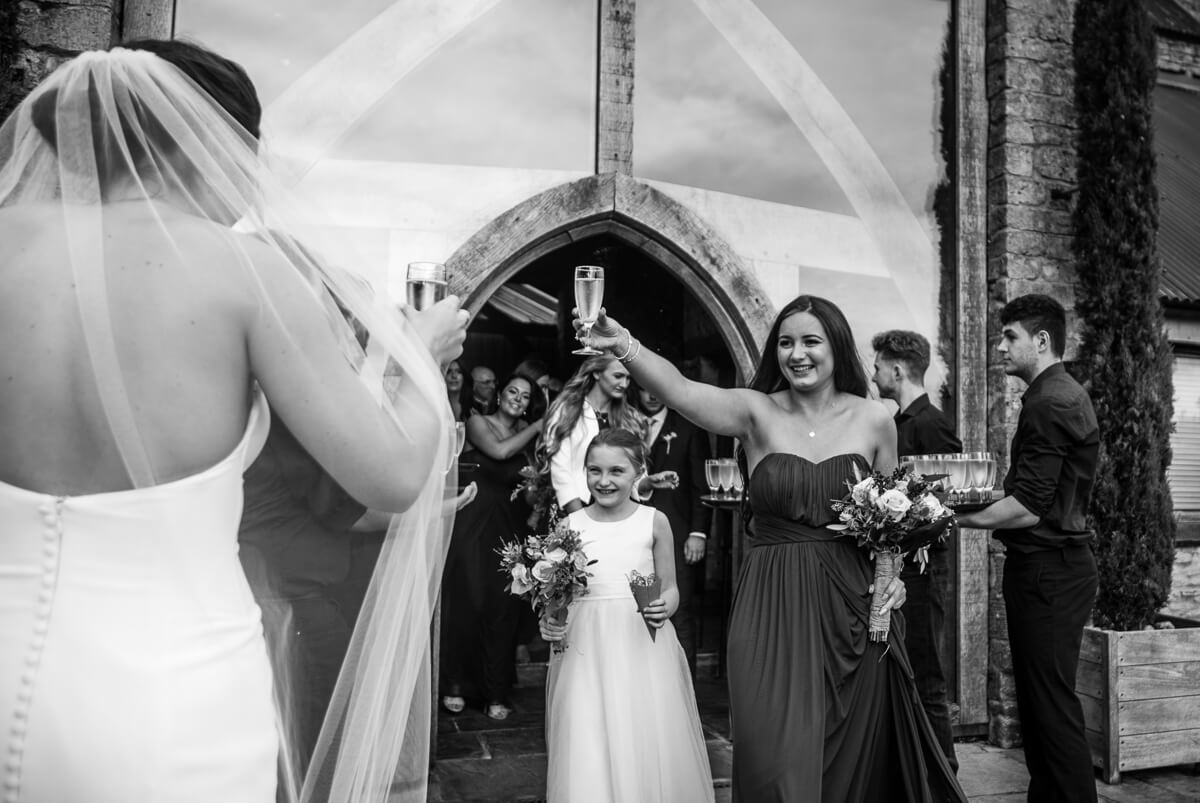 Bride is greeted by flower girl and bridesmaids after wedding ceremony