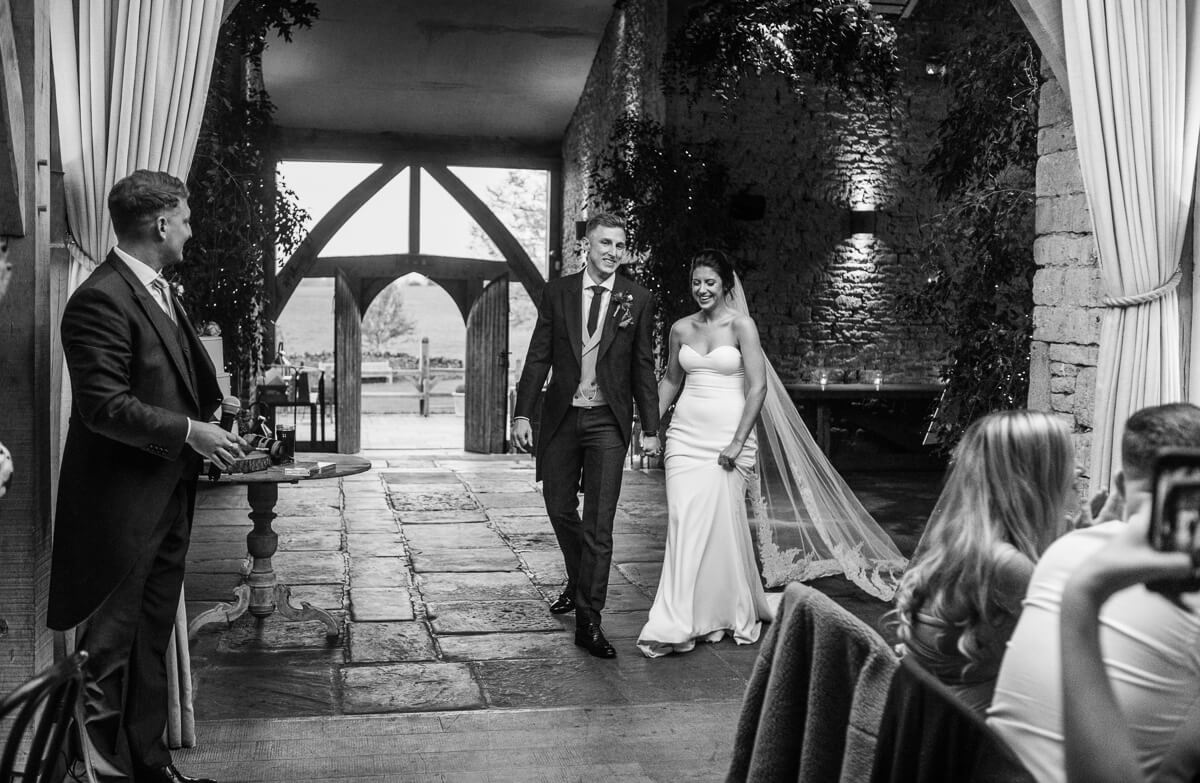 Black and white photo of bride and groom entering dining room
