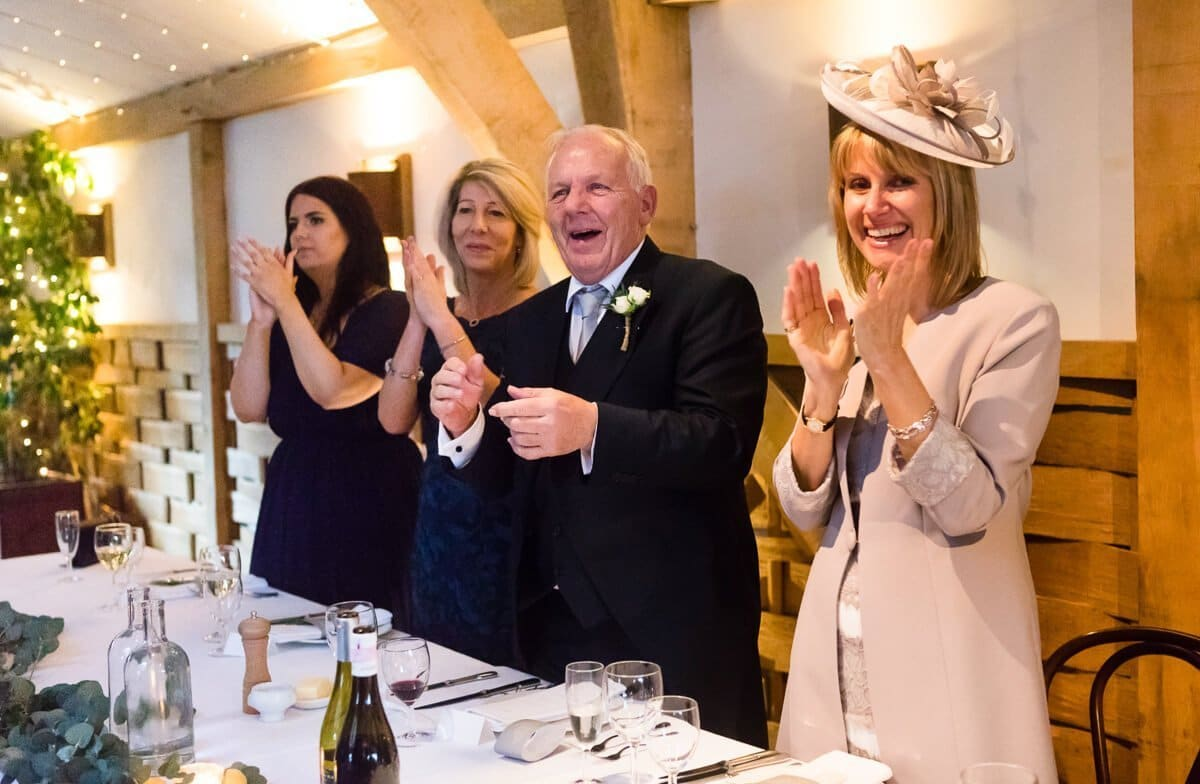 Family cheer as bride and groom enter dinning room