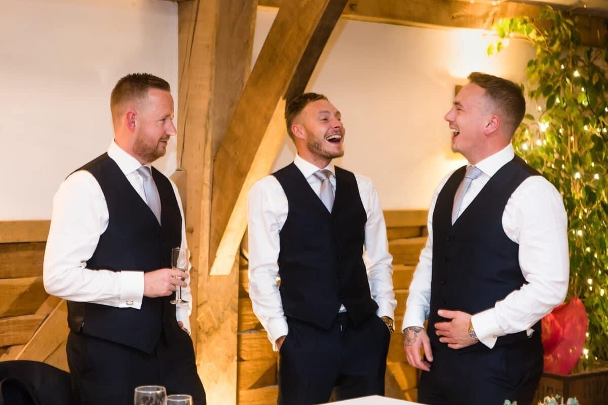 Groomsmen share a joke at wedding reception
