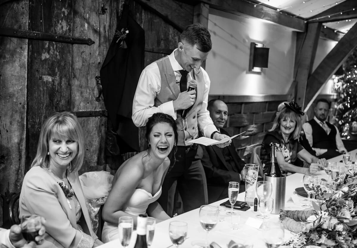 Bride laughing at her husbands wedding speech