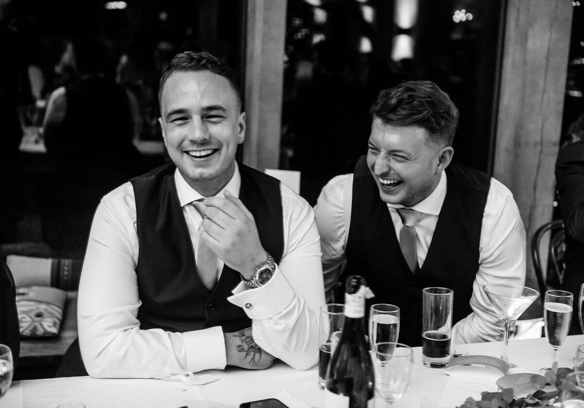 Groomsmen laughing at wedding speeches
