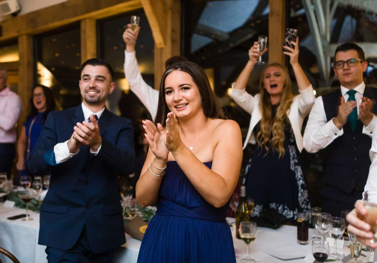 Wedding guests cheering and clapping at Cripps Barn