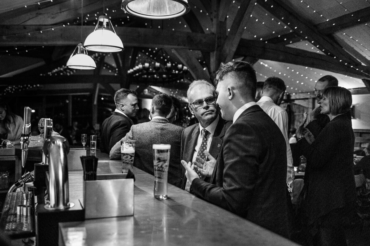 Wedding guests in conversation at bar
