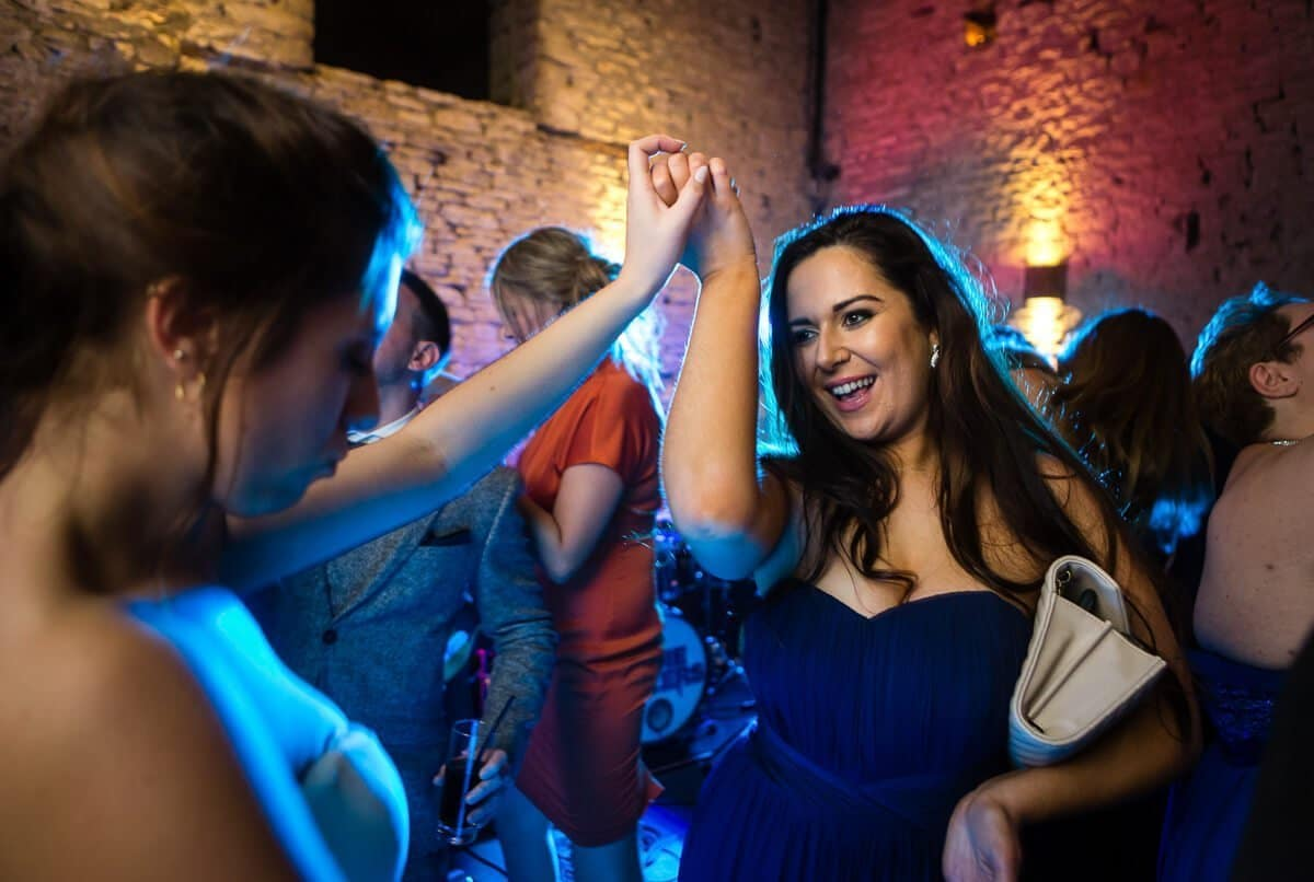 Bridesmaid dancing with bride at Cotswold wedding Cripps Barn