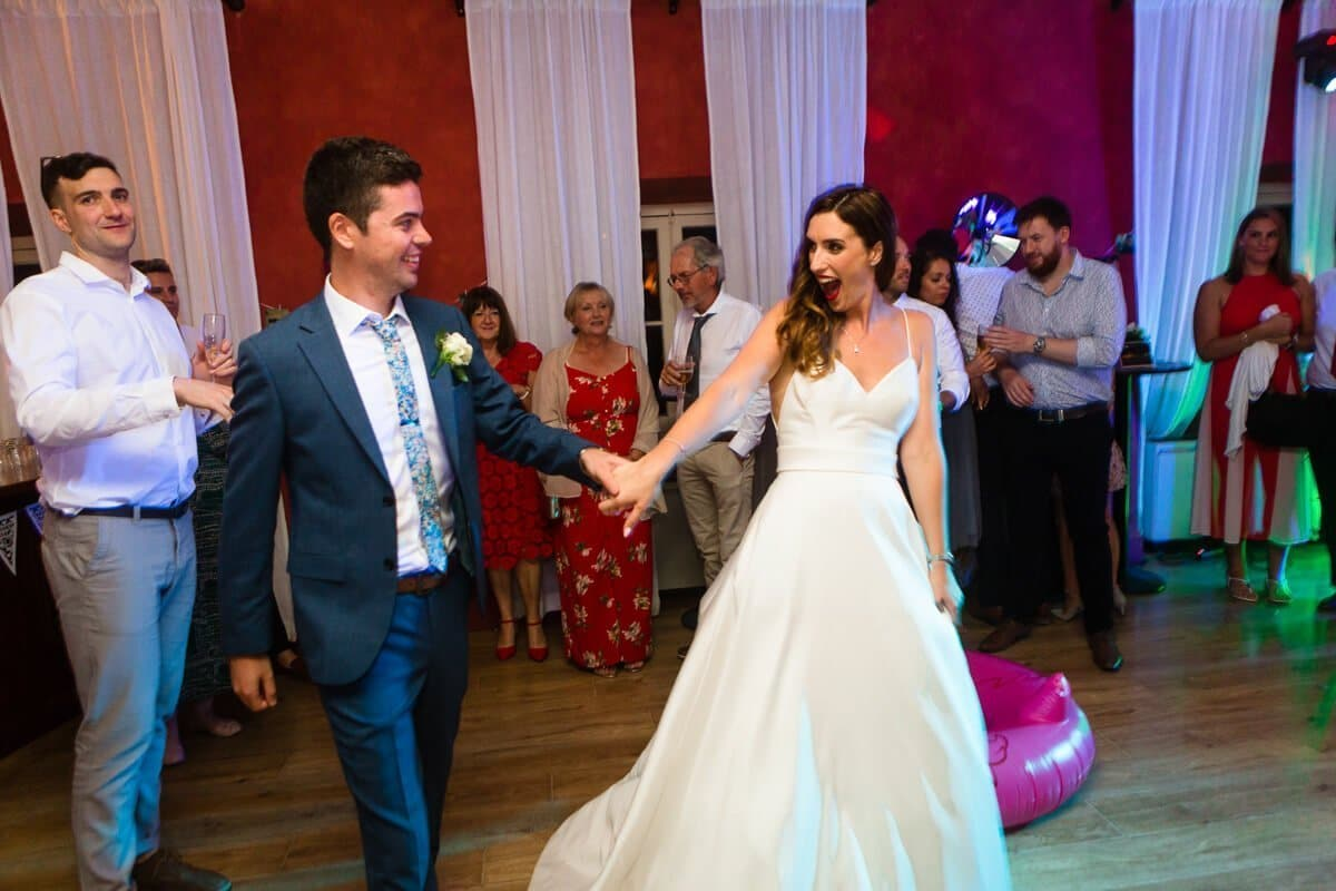 Bride and groom walk on to the floor for first dance at Spanish Wedding