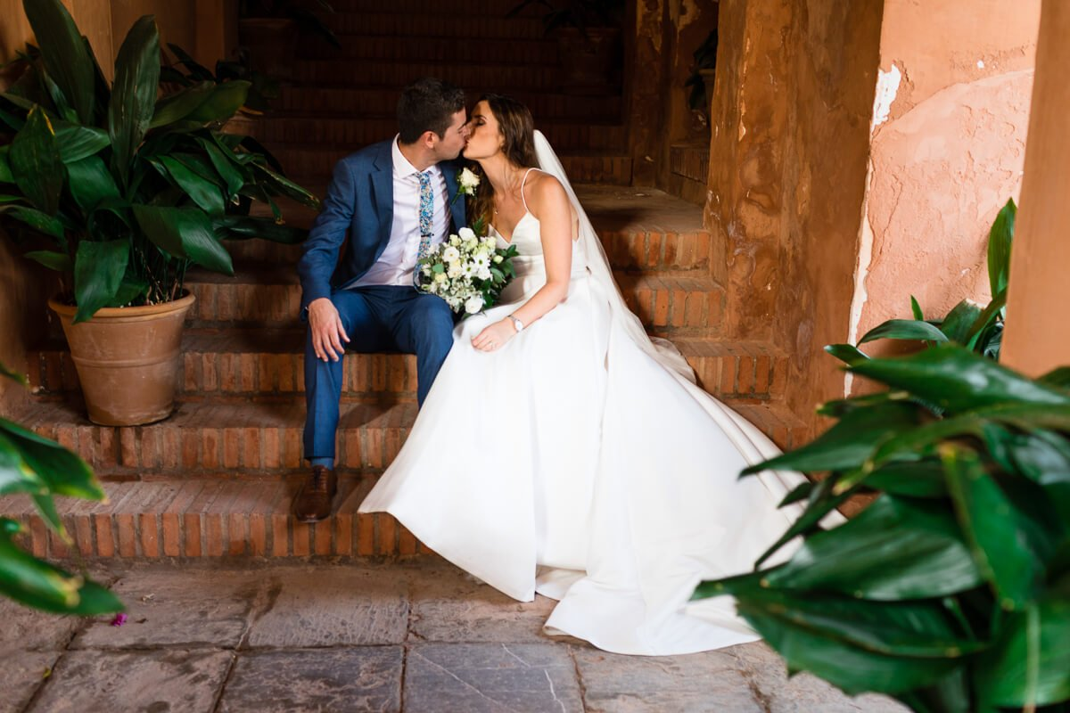 Portrait of couple kissing on Spanish steps at wedding